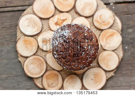 Chocolate muffin on a wooden stand on a light background