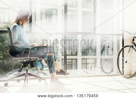 Hipster Girl using Notebook sunny Loft Studio.Student Researching Process Work.Young Business Woman Working Creative Startup modern Office.Analyze new marketing strategy.Blurred, film effect.Horizontal