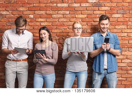 Contemporary gadgets overcame personal communication. Cheerful man and woman are standing and using tablets. Their friends are holding laptop and mobile phone. They are smiling