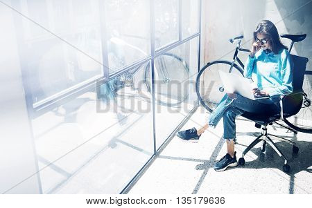 Hipster Girl using Laptop modern and sunny Loft Studio Office.Student Researching Process Work Time.Young Business Woman Creative Startup.Panoramic windows background.Blurred, film effect.Horizontal