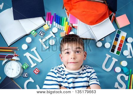 child lying on blue blanket with various school accessories