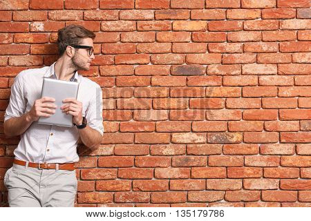 Smart young man is standing and holding a tablet. He is leaning on wall and looking aside with seriousness. Copy space in right side