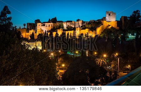 The view of lighted Alkazaba and streets below with street lights in Malaga Spain