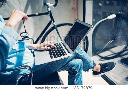 Work process modern design Studio Loft.Creative manager working coworkers office new freelance business startup.Using Laptop knees, holding glasses hand.Reflection screen.Horizontal.Film effect.Blurred