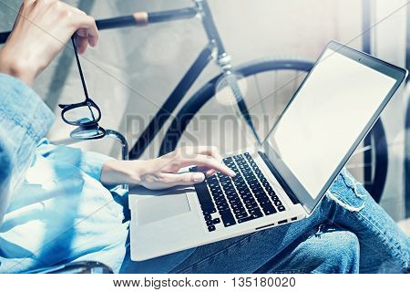Work process modern design Studio Loft.Creative manager working coworker office new freelance business startup.Using Laptop knees, holding glasses hand.Reflection.Horizontal mockup.Film effect.Closeup