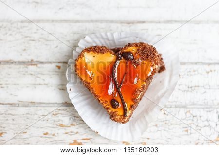 Coffee cake in the shape of a heart on a white wooden background