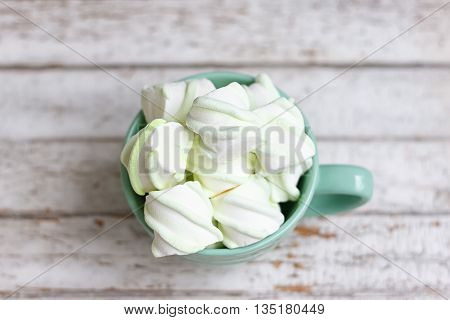 Peppermint large marshmallows in a large green cup on white wooden background