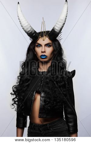 beautiful girl with horns on his head. girl on a black background. fone.rogi horns on the black color. sexy girl in a black jacket. woman without underwear