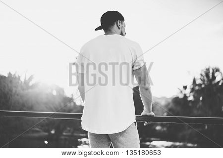 Photo Bearded Muscular Man Wearing Blank t-shirt, snapback cap and shorts in summer time. Green City Garden Park Sunset Background. Back view. Horizontal Mockup.Black White.