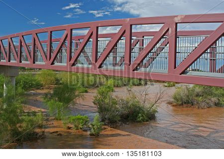 Red pedestrian bridge against a blue sky with clouds over river bed with running muddy water after a storm and green bushes