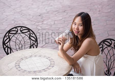 Beautiful asian girl in white dress sitting on a chair and drinks through a black straw a chocolate cold drink in a cup.