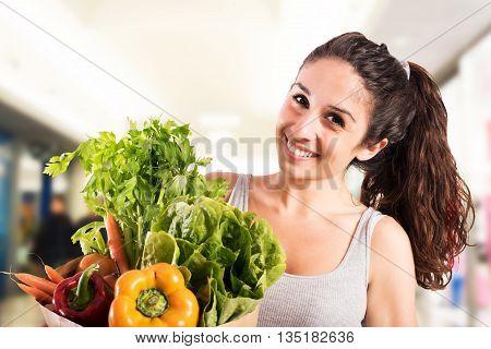 Smiling girl at supermarket with bag of vegetables