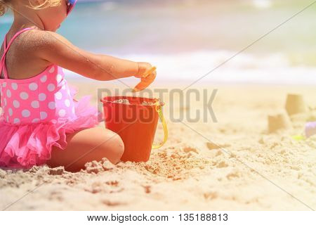 little girl play with sand on beach, family vacation