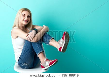 Portrait of cheerful young woman sitting on stool. She is raising her legs up and smiling. Isolated and copy space in right side