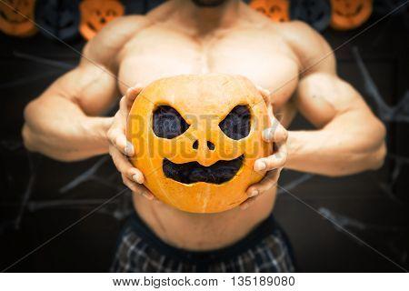 gym halloween theme gym halloween gourd bodybuilder with pumpkin in his hands, a strong man squeezes a pumpkin, sportsman's trunk, strong hands squeeze Halloween pumpkin