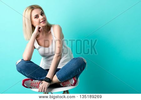 Portrait of attractive young woman waiting for someone. She is sitting on chair in lotus position. The lady is leaning head on arm and smiling. Isolated and copy space in right side