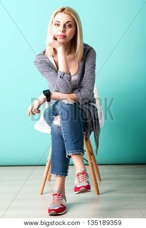 Full length portrait of pretty young woman sitting on chair with anticipation. She is looking at camera and leaning head on arm with boredom