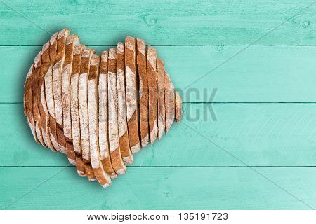 Sliced Bread Loaf Shaped As Heart Over Green Wood