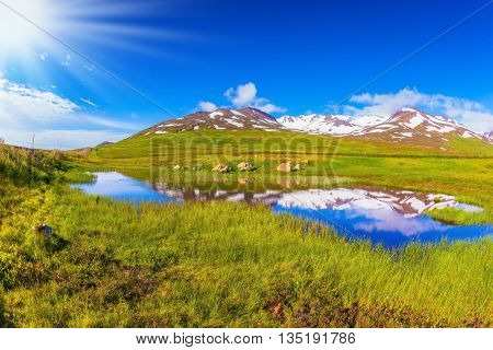 Summer Iceland. Blue lake water reflects snow hills. Fields grew with  fresh green grass