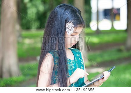 Closeup portrait young girl typing on digital tablet isolated outside outdoors background