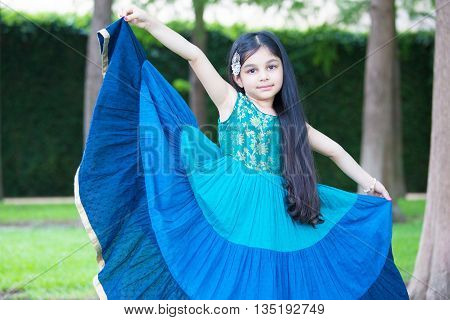 Closeup portrait pretty young girl showing off aqua blue dress isolated green trees grass isolated outside outdoors background