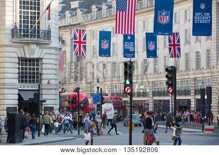 LONDON, UK - OCTOBER 4, 2015: Regent street decorated with British flags. Lots of people walking from shop to shop and public transport, taxis, cars and buses on the road