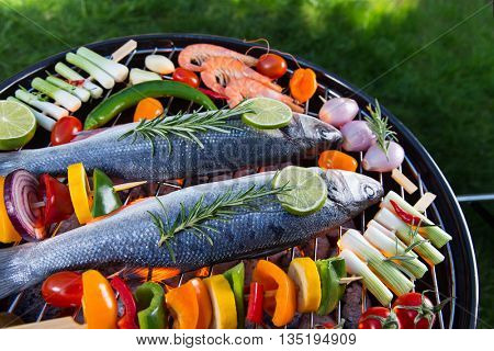Barbecue grill with sea fishes on green grass, close-up.
