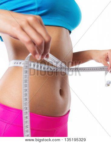 Slim girl measuring her waist, close-up.