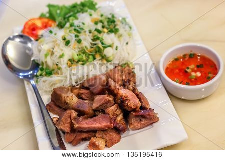 grilled pork with rice noodle in the white place with chilli dipping sauce
