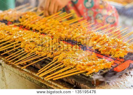 people grilled pork satays on the stove oven thai style