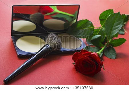 Dry textured correcting powder brush and rose on red surface. Rose reflecting in the mirror. Makeup product to even out skin tone and complexion. Professional cosmetics. Artistic retouching.