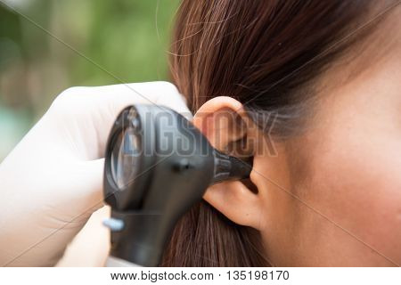 woman doctor monitors the patient's ear with equipment