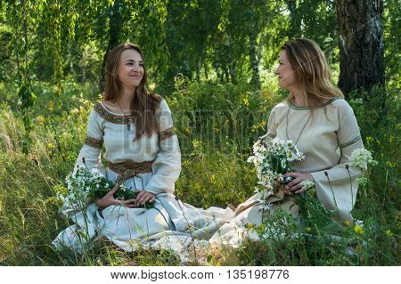 Attractive women in traditional russian clothes relaxing at nature background. Ivan Kupala Holiday Celebration
