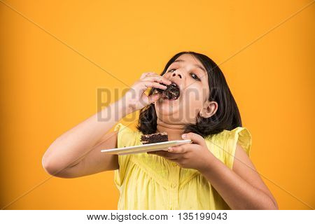 portrait of Indian kid eating cake or pastry, cute little girl eating cake, girl eating chocolate or strawberry cake over red background
