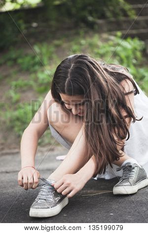 teen girl in park binding shoelace summer day