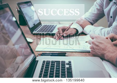 Businessman writing with laptop, pen and paper on table, close up of hands. With SUCCESS word