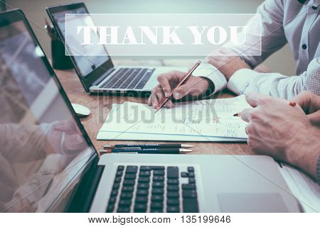 Businessman writing with laptop, pen and paper on table, close up of hands. With THANK YOU word