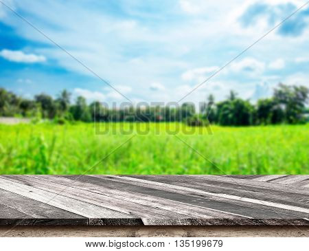 Empty Diagonal Wooden Table Top At Blurred Green Field And Blue Sky,template Mock Up For Display Of
