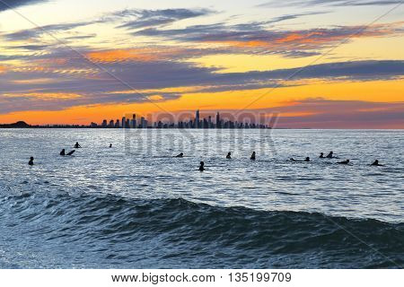 Currumbin Rock Gold Coast sunset with surfer silhouettes in ocean