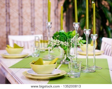 Beautiful table setting with white and green colors. Shallow DOF