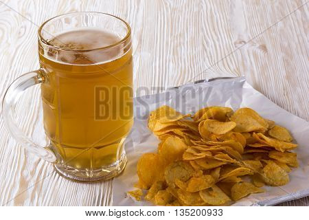 Potato chips and glass of beer on a wooden table.