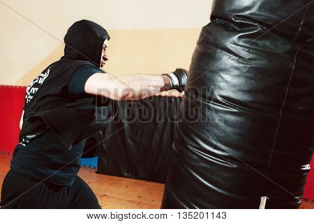 Boxer beating punching bag at gym. Prize-fighter training close-up. Male boxer in black sportsuit kicking punching bag. Intensive training before fight