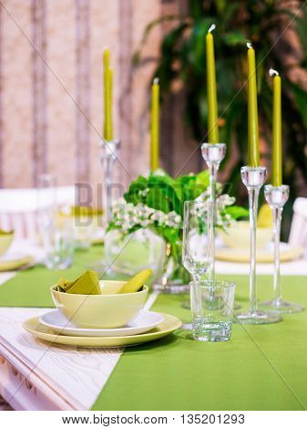 Beautiful table setting with white and green colors. Vertical composition. Shallow DOF