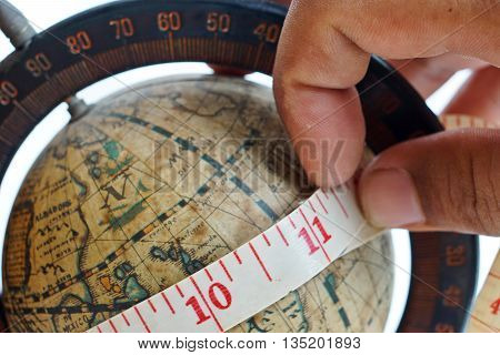 close up of vintage global map with measuring tape around