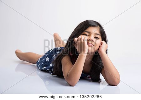 indian cute girl lying on the floor resting her head in her hands, asian Little girl laughing, lying on her stomach, isolated over white background