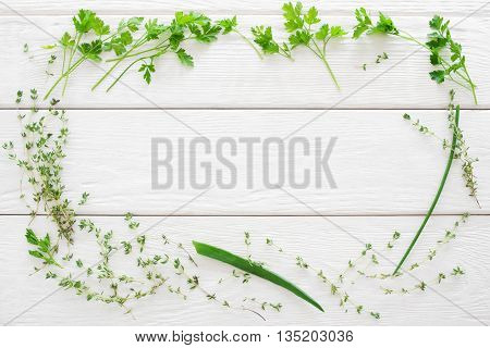 Thyme, parsley and chives frame on white wood flat lay. Top view on herbs put in the form of frame on white wooden background. Copyspace for advertisement