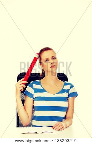 Teenage woman doing homework and holding huge pen