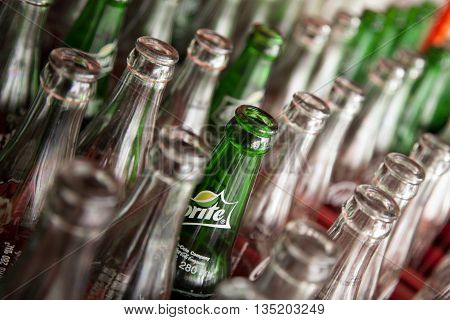 Pattaya Thailand - March 28 2016: Soda empty bottle with Sprite logo among usual bottles. Many used bottles arranged in rows for recycling background