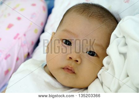 Baby girl looking something on her bed. Cute baby in white dress is looking something.