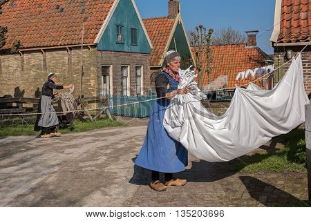 ENKHUIZEN, NORTH-HOLLAND / THE NETHERLANDS - APRIL 11, 2016: Actors in national costumes involved in household chores in the open-air museum of the city of Enkhuizen